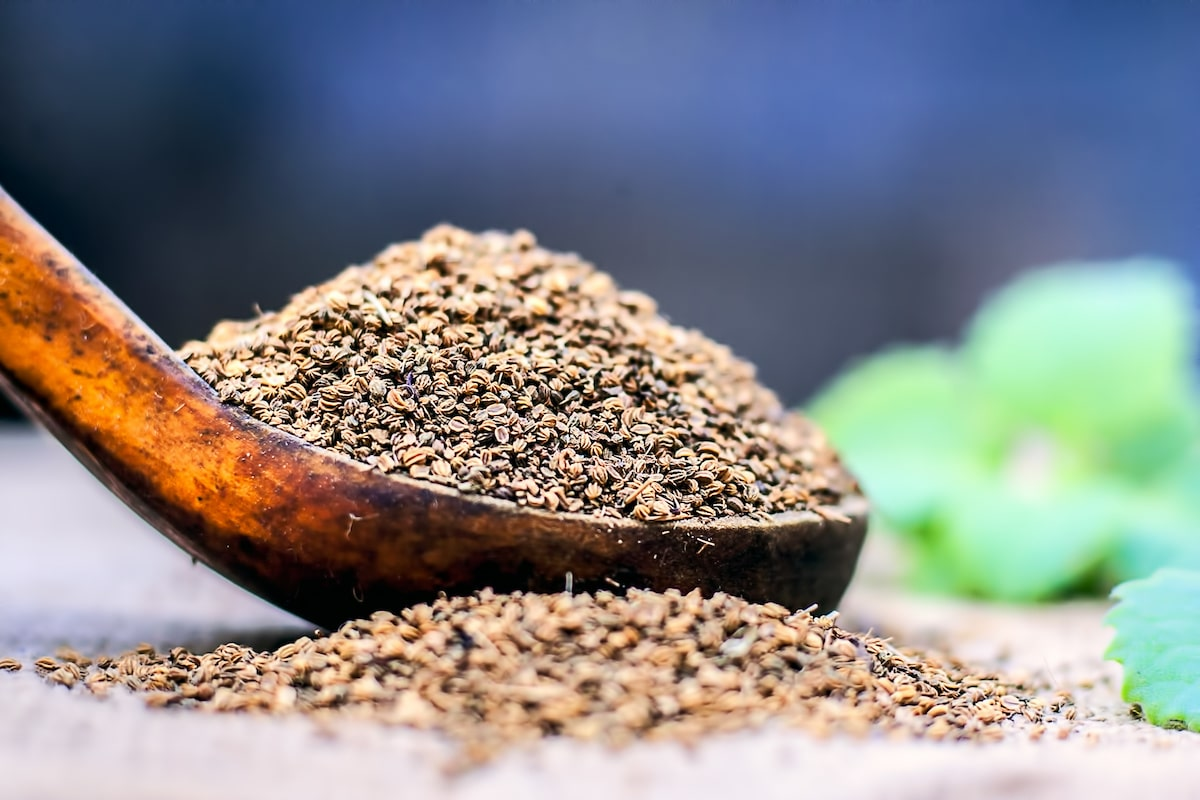 Trachyspermum ammi, Ajwain seeds in a wooden scoop with some leaves on a gunny background.